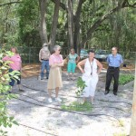 Mary Dewey leads a group after meeting to view here community garden.